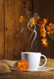 Cuvette de café avec les fleurs oranges Images libres de droits