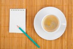 Cuvette de café blanc de carnet sur le fond en bois Photographie stock libre de droits