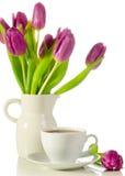 Cuvette de café blanche avec le groupe de tulipes pourprées sur le petit morceau Photo stock