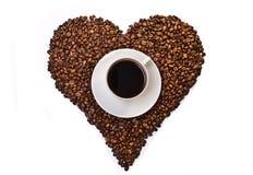 Cuvette de café blanche sur les grains de café en forme de coeur Photographie stock libre de droits