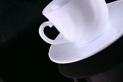 Cuvette de café en céramique avec une soucoupe sur la glace foncée Photographie stock