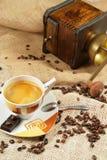 Cuvette de café entourée par des graines de café image stock