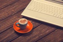 Cuvette de café et d'ordinateur portatif Photographie stock libre de droits