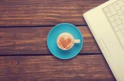 Cuvette de café et d'ordinateur portatif Photo stock