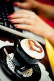 Cuvette de café et de la main de la dame travaillante Photo libre de droits