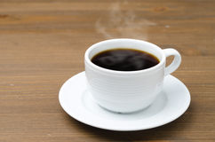 Cuvette de café noir avec la vapeur sur une table en bois brune Images stock