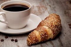 Cuvette de café noir et de croissant Photographie stock