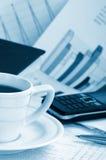 Cuvette de café parfumé sur des affaires de papier de matin Image libre de droits