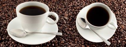 Cuvette de café sur des grains de café Photos stock