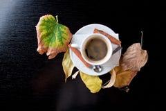 Cuvette de café sur la table en bois avec des lames d'automne photos stock