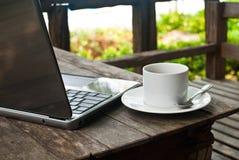 Cuvette de café sur le bois avec l'ordinateur portatif. Image stock