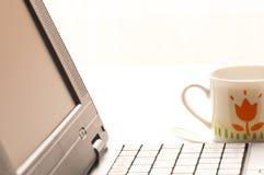 Cuvette de café et d'ordinateur portatif sur la table Photographie stock libre de droits