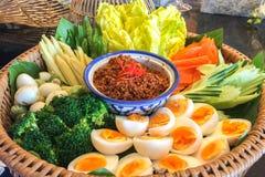 Cuvette de Chili Paste avec le divers type des légumes frais et d'oeufs dans le grand panier de rotin Image stock