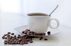Cuvette de Coffe et haricots de coffe sur une table Image libre de droits