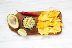 Cuvette de guacamole et d'ingrédients mexicains traditionnels avec le nacho image libre de droits