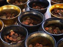 Cuvette de l'aumône du moine avec la pièce de monnaie mise photos stock