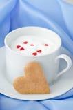 Cuvette de lait chaud avec de la mousse, décorée des coeurs de sucre et du coeur Photographie stock