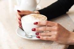 Cuvette de matin de cappuccino et main d'une fille avec Photo libre de droits