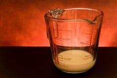 Cuvette de mesure avec du lait Photographie stock libre de droits