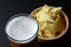 Cuvette de pommes chips et d'un verre de bière de blé Photo libre de droits