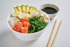 cuvette de poussée avec des saumons, avocat, riz, salade de Chuka, oignons doux, oeufs de caille arrosés avec le sésame blanc et  image libre de droits