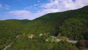 Cuvette de route d'enroulement le passage de montagne de forêt salut en Transylvanie, Roumanie Vue aérienne d'un bourdon Voitures clips vidéos