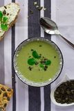 Cuvette de soupe à crème de brocoli, de pain de grain avec des graines de citrouille et de cuillère sur la table, concept végétar photo stock