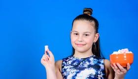 Cuvette de sourire de prise de visage de fille avec le fond bleu doux de guimauves ? disposition Doux et doux Concept de pied de  images stock
