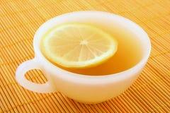Cuvette de thé avec le citron dans la lumière d'or chaude Photos libres de droits