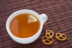 Cuvette de thé avec le citron et le biscuit un casseur Photos stock