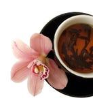 Cuvette de thé avec les orchidées roses de la plaque noire d'isolement Photographie stock
