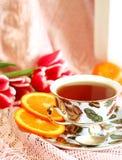 Cuvette de thé, d'orange et de tulipes Photographie stock libre de droits