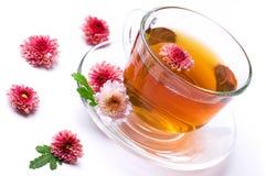 Cuvette de thé de fines herbes avec des fleurs sur le blanc Photos stock