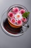 Cuvette de thé de fines herbes avec des fleurs sur le noir Image stock