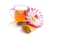 Cuvette de thé de fines herbes avec la fleur sur l'essuie-main d'isolement Photo stock