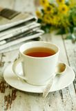 Cuvette de thé, de journal et de fleurs sur vieil en bois Photo stock