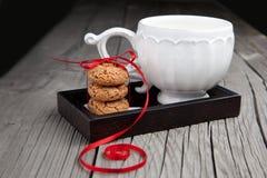 Cuvette de thé et de biscuits sur le fond en bois Images libres de droits