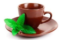 Cuvette de thé vert sur la soucoupe avec la menthe d'isolement Photographie stock libre de droits