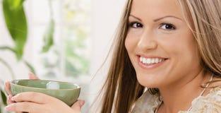 Cuvette de thé heureuse de fixation de femme Image stock