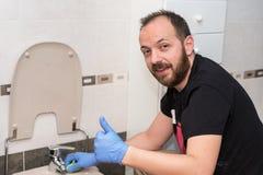 Cuvette des toilettes de nettoyage d'homme Émotion positive montrant des pouces  images libres de droits