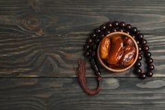 Cuvette en bois avec des dates et des perles de prière sur le fond en bois photos stock