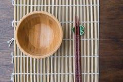 Cuvette en bois de vue supérieure avec des baguettes sur le tapis en bambou sur la table en bois Image libre de droits