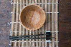 Cuvette en bois de vue supérieure avec des baguettes sur le tapis en bambou sur la table en bois Photo libre de droits