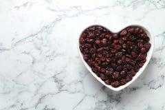 Cuvette en forme de coeur avec des canneberges sur la table de marbre, vue supérieure avec l'espace pour le texte images libres de droits