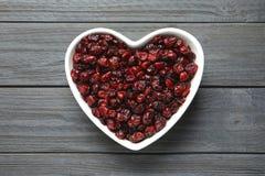 Cuvette en forme de coeur avec des canneberges sur le fond en bois, vue supérieure Fruits secs photographie stock libre de droits