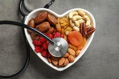 Cuvette en forme de coeur avec les fruits, les écrous et le stéthoscope secs sur le fond gris photo stock