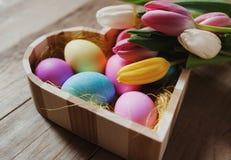 Cuvette en forme de coeur, oeufs colorés et tulipes - Joyeuses Pâques Photos libres de droits