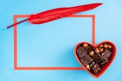 Cuvette en forme de coeur rouge avec des morceaux de chocolat, cadre rouge et rouge Image stock
