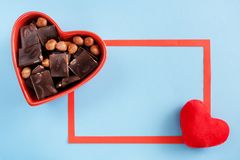 Cuvette en forme de coeur rouge avec du chocolat, cadre rouge et peluche rouge h Photographie stock