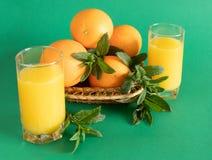 Cuvette en osier avec les oranges et la menthe sur le fond vert photos libres de droits